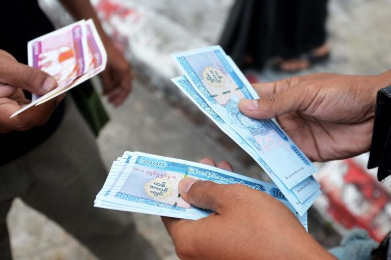 People hold new kyat banknotes featuring a portrait of the late general Aung San, outside Myanmar Economic Bank in Nay Pyi Taw on January 7. (AFP)