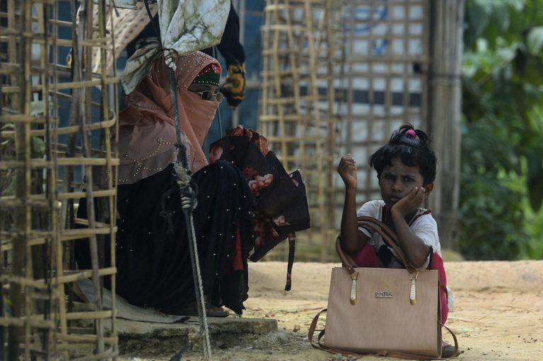 A Rohingya refugee girl waits for transportation with her mother at Kutupalong refugee camp in Ukhia on October 15. (AFP)