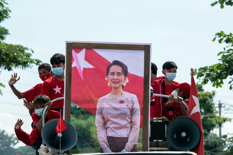 Children in National League for Democracy t-shirts take part in a campaign convoy behind a portrait of party leader Daw Aung San Suu Kyi in Yangon on October 25. (AFP)