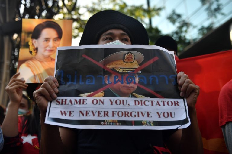 A Myanmar migrant holds up a poster with the image of Tatmadaw commander-in-chief Senior General Min Aung Hlaing at a demonstration outside the Myanmar embassy in Bangkok on February 1. (AFP)