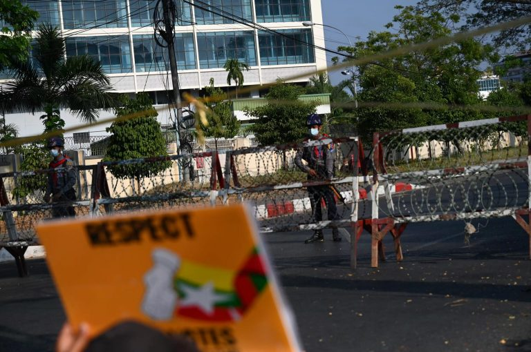 Police look on behind a barricade as protesters hold a demonstration outside the Central Bank of Myanmar branch in Yangon on February 16. (Frontier)