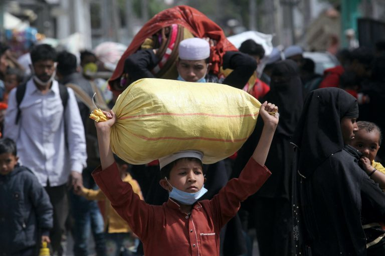 Rohingya refugees carry their belongings as they leave a Rohingya refugee camp in Jammu on March 7, 2021. (AFP)