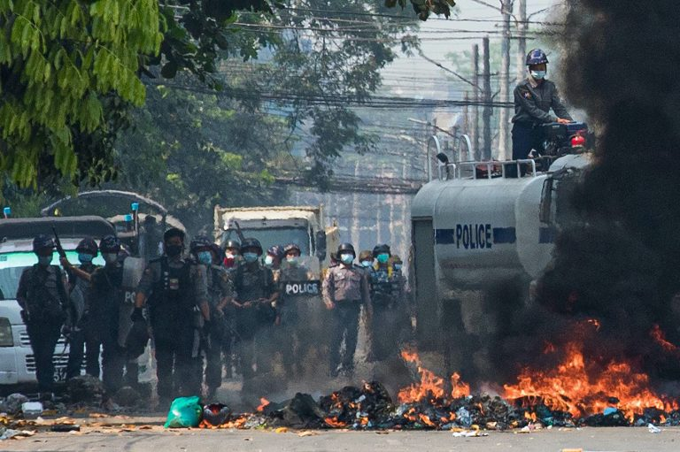 Security forces gather behind a burning barricade during a crackdown on protests against the military coup in Yangon on March 17. (AFP)