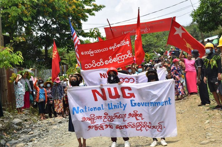 Protesters marching with banners supporting the opposition National Unity Government (NUG) during a demonstration against the military coup in Hpakant in Myanmar's Kachin state in May 2021. (KACHINWAVES/AFP)