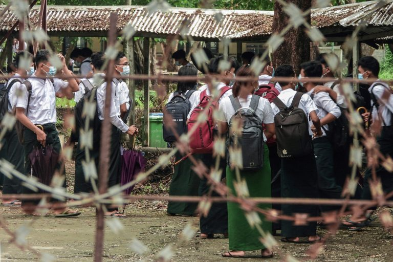 Students wait outside classrooms in Sittwe, capital of western Rakhine State on June 1, 2021. - Schools in Myanmar opened on June 1 for the first time since the military seized power, but teachers and students are set to defy the junta's calls for full classrooms in a show of resistance. (Photo by STR / AFP)