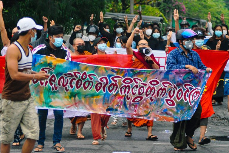 Buddhist monks walk with protesters as they hold a banner that reads,