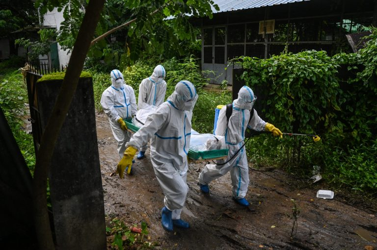 Volunteers wearing personal protective equipment carry the body of a victim of the Covid-19 coronavirus to a cemetery in Hlegu Township in Yangon on July 10, 2021. (AFP)
