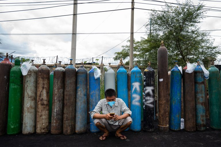 A man using his mobile phone in front of empty oxygen canisters outside a factory in Mandalay on July 31, 2021. (AFP)