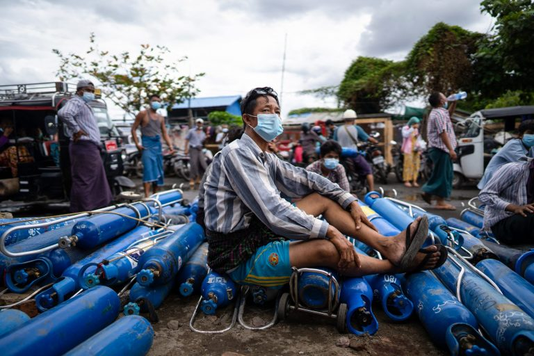 A man sitting on empty oxygen canisters outside a factory in Mandalay on July 13, 2021 (AFP)