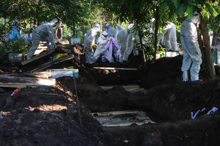 Volunteers wearing personal protective equipment bury the bodies of people who died from the Covid-19 coronavirus after their funeral at a cemetery in Mandalay on July 14, 2021. (AFP)