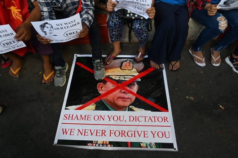 Protesters step on a banner showing an image of Myanmar military chief Senior General Min Aung Hlaing during a demonstration against the military coup in Yangon on February 1, 2021. (AFP)