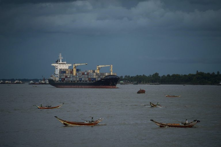 A container ship anchors along the Yangon river as traditional wooden boats ferry passengers across in 2016. (AFP)