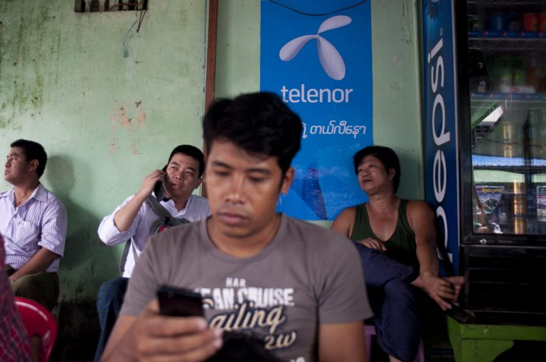 A man uses the internet with a mobile phone in front of a sign advertising Telenor in Yangon on September 26, 2014, shortly after the Norwegian operator launched its network. (AFP)