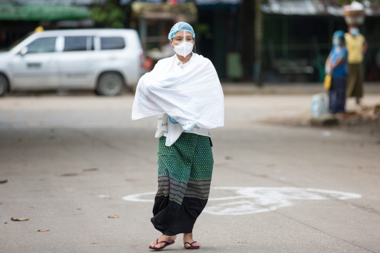 A woman carrying a baby walks towards a polling station in Botahtaung Township to cast her vote on November 8. This photo went viral on election day – but without a credit for the photographer. (Thuya Zaw | Frontier)
