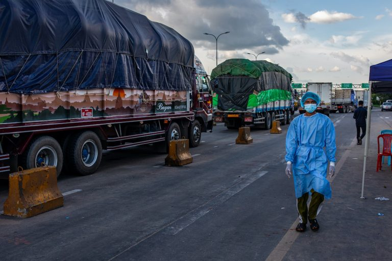 A medical worker walks past trucks lined up at a toll gate along the Yangon-Mandalay Highway, their drivers waiting to be tested for COVID-19. Travel restrictions and COVID-19 transport protocols have caused major disruptions to the country's logistics network. (Hkun Lat | Frontier)