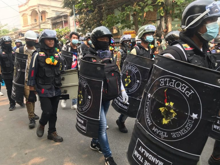 Pro-democracy protesters are seen on March 13 carrying makeshift shields to defend themselves from increasingly lethal crackdowns by security forces in Mandalay. (Frontier)