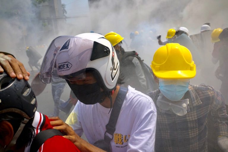 Protesters are caught in a cloud of tear gas near Insein Road late this morning. (Frontier)