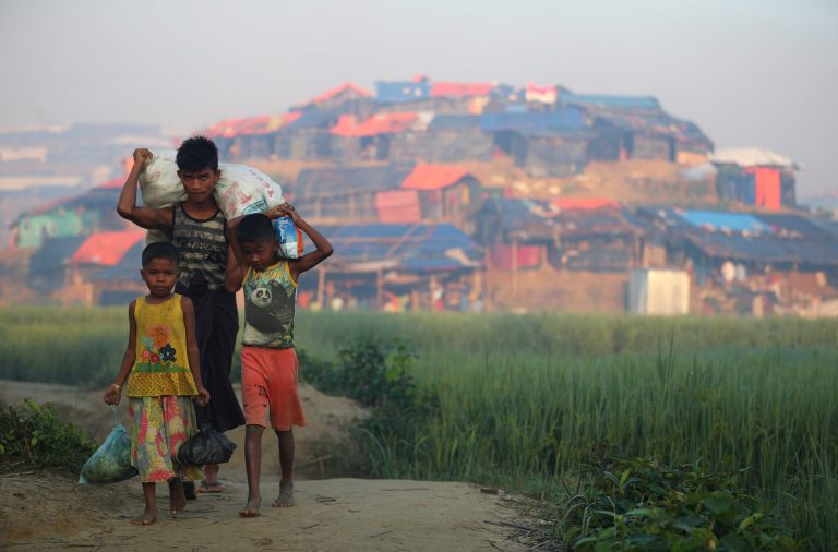 Rohingya children carry sacks of donated food outside of a Rohingya refugee camp in Bangladesh. (AFP)