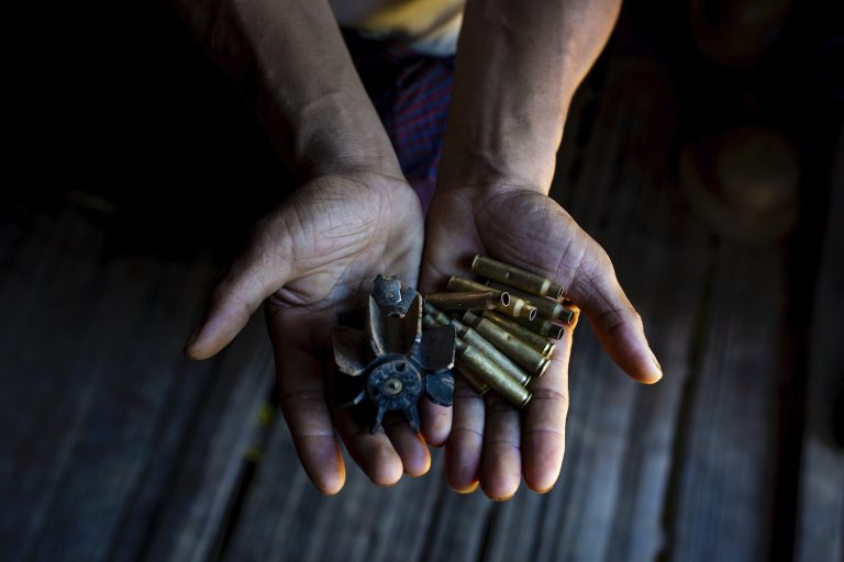 A villager holds out bullet shells collected from Pang Kyin village in Shan State's Kyaukme Township on August 4. (Hkun Lat | Frontier)