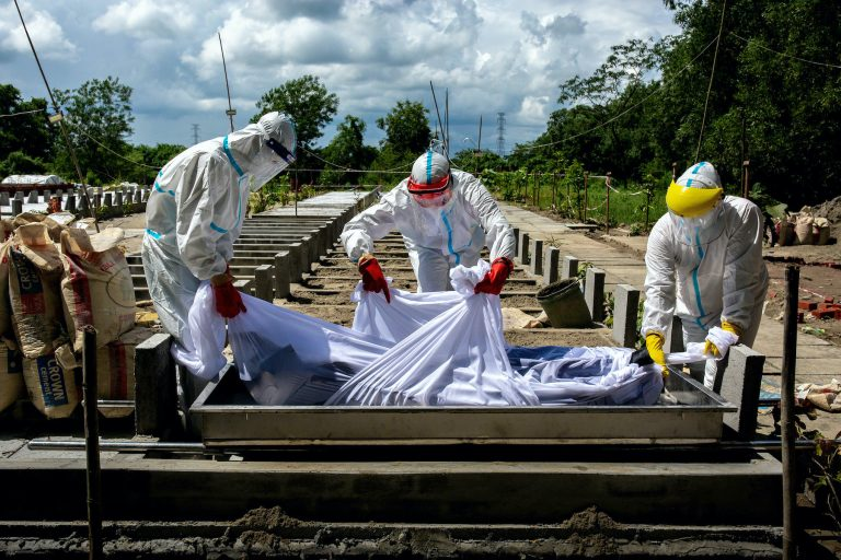 Volunteers bury the body of a deceased COVID-19 patient at the Hteinbin cemetery in Yangon on October 23. (Hkun Lat | Frontier)