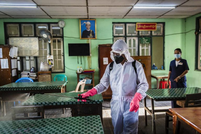 A member of Yangon City Development Committee wearing protective clothing disinfects a YCDC office in Kyimyindaing Township as part of preventative measures against the spread of COVID-19 in Yangon on 25 March. (Hkun Lat I Frontier)