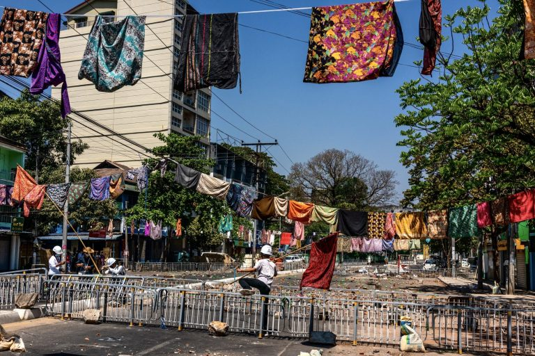 Rows of htamein hang above lines of barricades in the Kyaukmyaung area of Tarmwe Township on March 8. The women's garments are hung to deter superstitious members of the security forces. (Frontier)