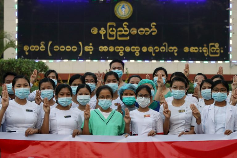 Striking medical staff hold up a three-finger salute in opposition to military rule at a government hospital in Nay Pyi Taw this morning. (AFP)