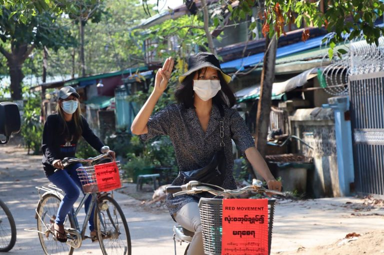 A Yangon resident raises the three-finger pro-democracy salute while protesting against military rule by bicycle on April 15. (Facebook / AFP)