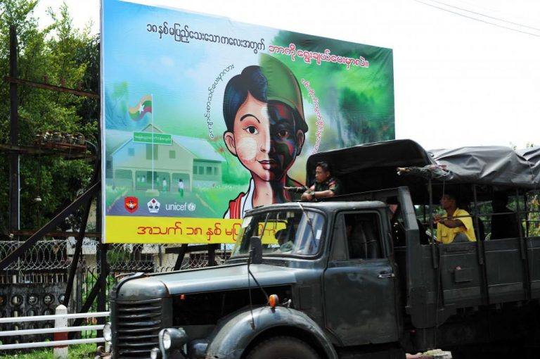 A Tatmadaw truck passes by a public sign stating that only people aged 18 or above can enlist in the military. (Steve Tickner | Frontier)