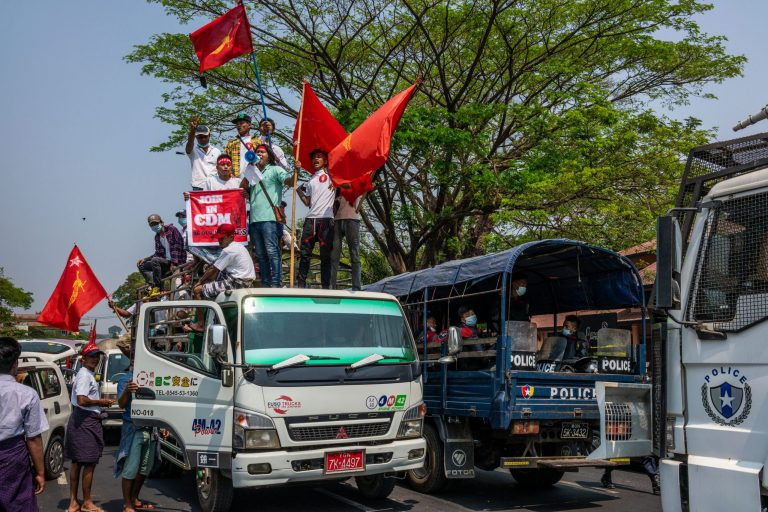 Protesters wave NLD flags and shout slogans beside a police truck during a protest against the military coup in Yangon on February 22. (Frontier)