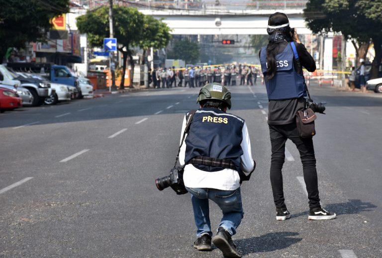 ရန်ကုန်မြို့၊ အနော်ရထာလမ်းမပေါ်ရှိ ဒီမိုကရေစီအရေးတောင်းဆိုနေသည့် ဆန္ဒပြသူများအနီး အသင့်အနေထားဖြင့် ရပ်စောင့်နေသည့် ရဲတပ်ဖွဲ့ဝင်များကို သတင်းမှတ်တမ်းရယူနေသော ဓာတ်ပုံသတင်းထောက်နှစ်ဦးကို ဖေဖော်ဝါရီ၂၈ရက်က မြင်တွေ့ရစဉ်။ (ဓာတ်ပုံ | ဖရွန်းတီးယားမြန်မာ)