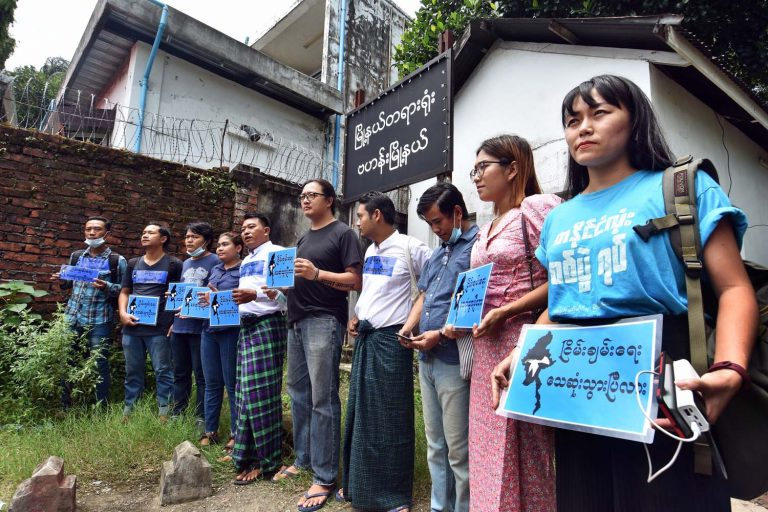 Activists charged over the anti-war rally in Yangon stand outside Bahan Township Court after their conviction for violating a protest law. (Steve Tickner | Frontier)