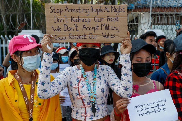 A protester outside the International Labour Organization office in Yangon holds up a sign decrying midnight arrests by security forces on February 17. (Frontier)