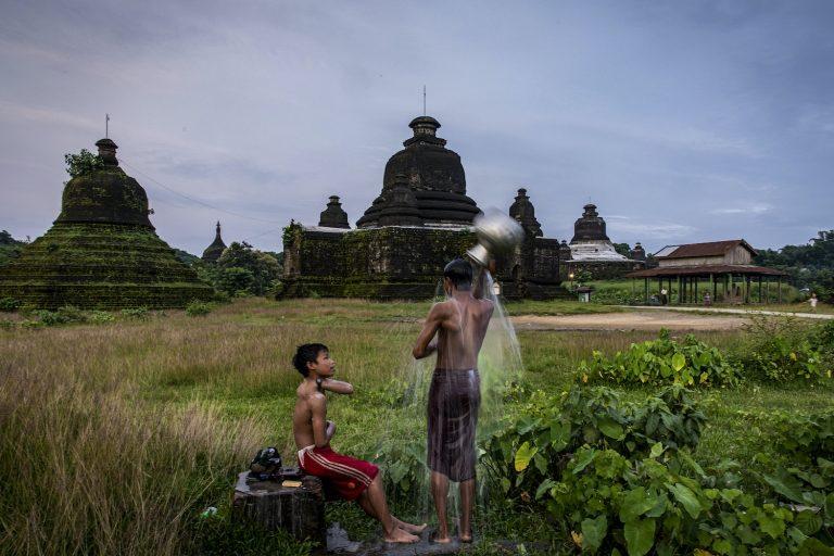 Children shower near a pagoda in Mrauk-U, Rakhine State on 21 August 2020. (Hkun Lat I Frontier)