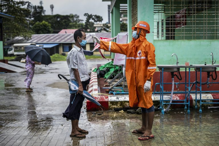 A volunteer checks the temperature of a visitor at the entrance to Sittwe General Hospital in Rakhine State on August 24. (Hkun Lat | Frontier)