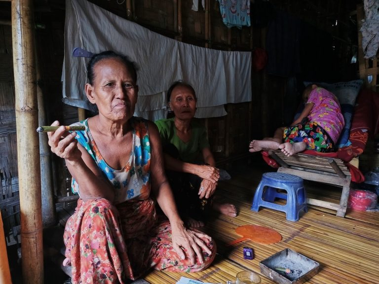 Daw Tin Tin, 66, smokes a cheroot in the informal housing she shares with relatives in the Yay Oak Kan section of Yangon's Hlaing Tharyar Township on May 1. (Frontier)