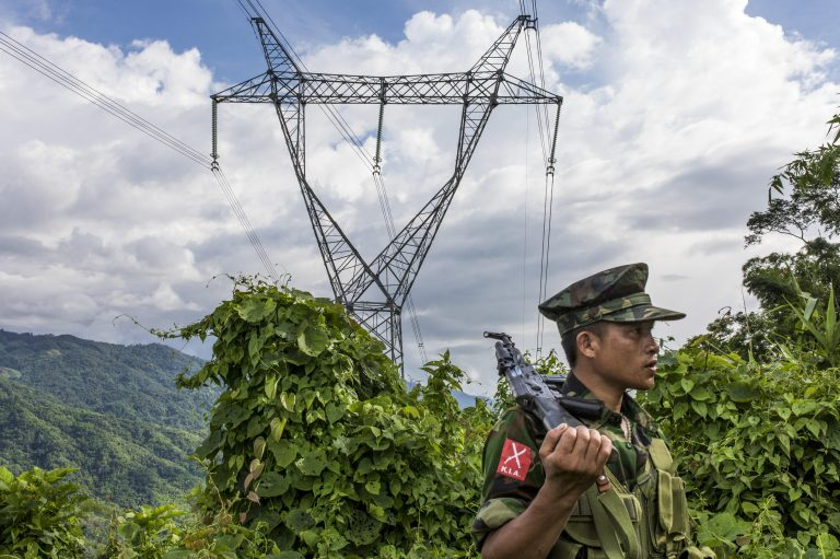 Kachin Independence Army soldiers stand on a mountain near powerlines. Photo by Hkun Lat