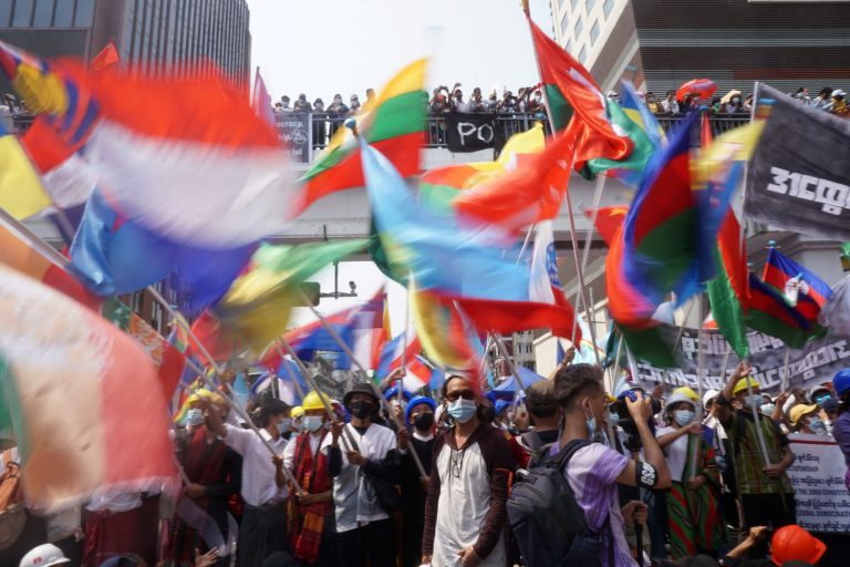 Protesters wave the flags of different ethnic nationalities while marching through Yangon on February 18 to oppose military rule. (AFP)