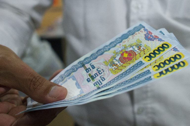 A man holds 10,000 kyat notes. (AFP)