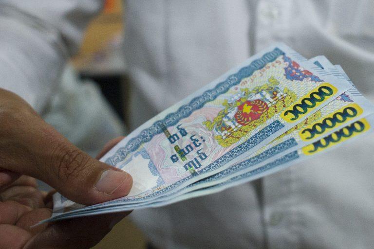 A man holds 10,000 kyat notes. (AFP)