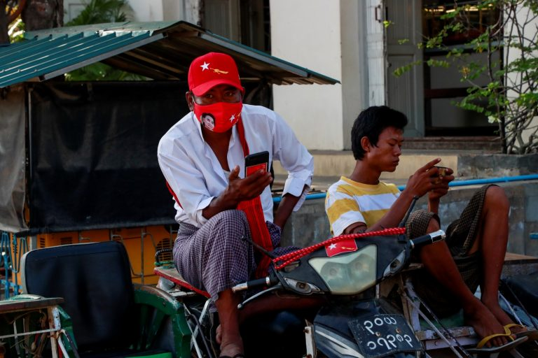 A motorcycle taxi driver in central Pyawbwe clad in the merchandise of the National League for Democracy, which is campaigning hard to unseat the Union Solidarity and Development Party in the township. (Nyein Su Wai Kyaw Soe | Frontier)