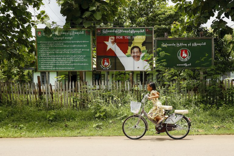 A girl cycles past a USDP campaign billboard in Bawlakhe Township, Kayah State, on August 21. (Nyein Su Wai Kyaw Soe)