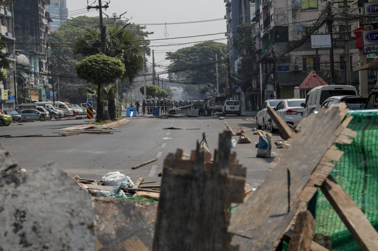 Police are seen above a barricade in Yangon on February 28. (Frontier)