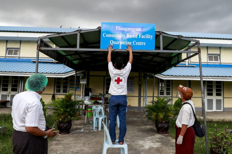 Myanmar Red Cross Society staff put up a sign at a quarantine facility in Yangon's Thingangyun  Township on September 10. (Nyein Su Wai Kyaw Soe | Frontier)