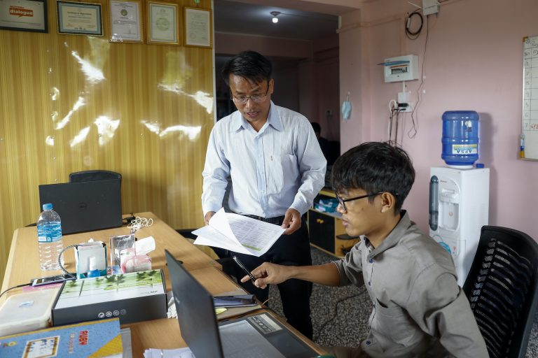 Ko Chan Lian, center, executive director of the domestic election observation group the Hornbill Organization – seen here with a coworker at the group's office in East Dagon Township, Yangon on July 14 – said the coronavirus has seriously hobbled the group's plans for the November election. (Nyein Su Wai Kyaw Soe | Frontier)