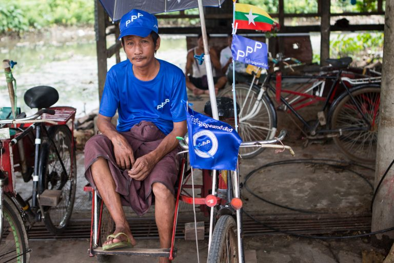 A Mayangone trishaw driver waits for customers while clad in People's Pioneer Party gear. (Thuya Zaw | Frontier)