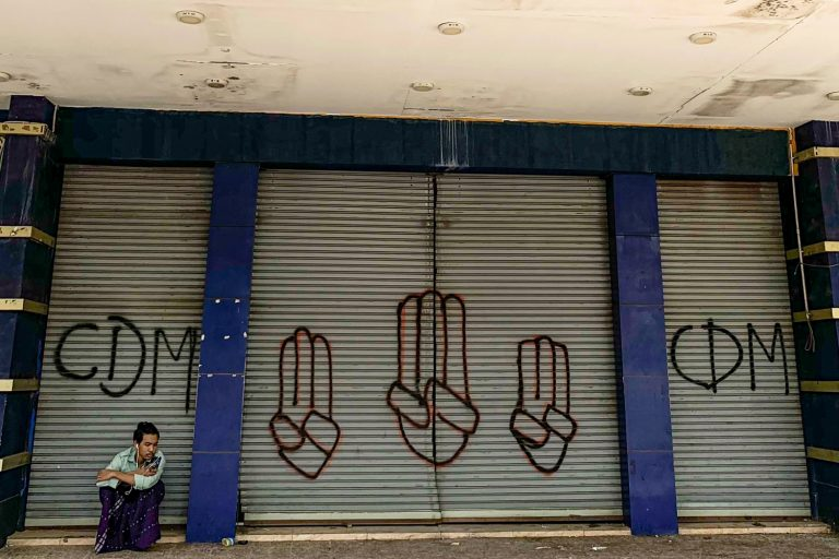 A man in Yangon on April 7 sits in front of shutters with the graffitied initials of the Civil disobedience Movement and the three-finger salute made by anti-coup protesters. (AFP)