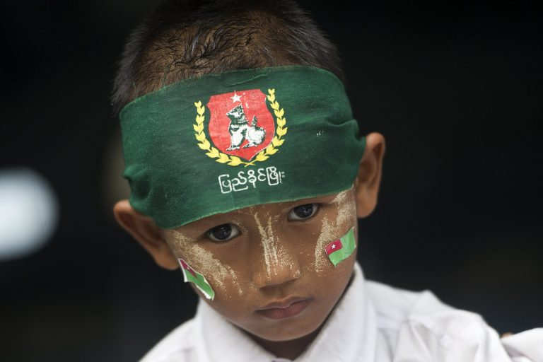 A boy wears a bandana and stickers with the symbols of the military-backed Union Solidarity and Development Party. (AFP)