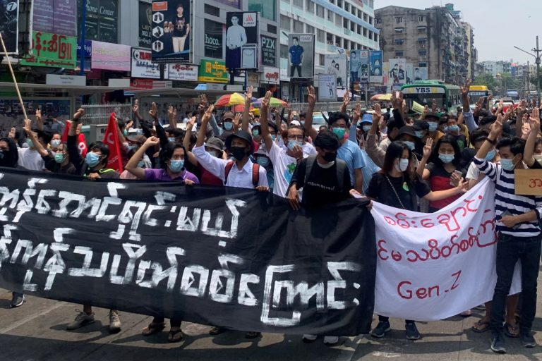 Anti-coup protesters hold up the three-finger salute while demonstrating in Yangon's Tarmwe Township on April 26. (AFP)