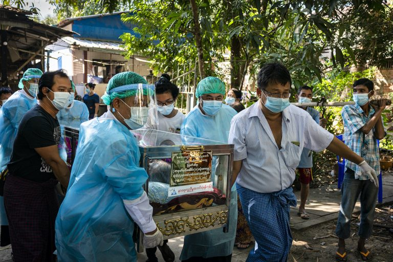 Volunteers with Yangon's Free Funeral Service Society transport a body from the deceased's home to the Yayway cemetery on December 11, 2020. (Hkun Lat   Frontier)